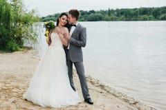 Abrazo de recienes casados en la orilla del río Fotografía de archivo