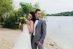 Abrazo de recienes casados en la orilla del río Fotos de archivo libres de regalías