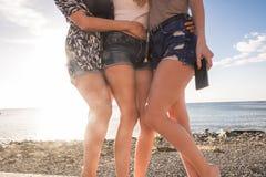 Abrazo de tres mujeres jovenes ellos mismos en un día soleado Imagenes de archivo