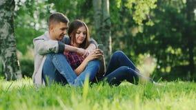 Abrazo del hombre y de la mujer, sentándose en la hierba en el parque Mirada de la pantalla del teléfono móvil almacen de video