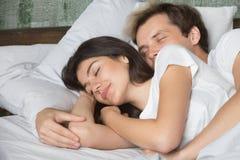 Abrazo del novio y de la novia dormido en cama acogedora Imagen de archivo