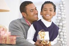 Abrazo del padre y del hijo, celebrando el regalo de la Navidad Imagen de archivo libre de regalías