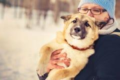 Abrazo del pastor Puppy y de la mujer del perro al aire libre Foto de archivo