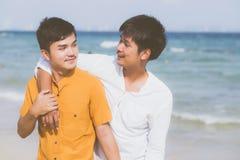 Abrazo derecho de los pares asiáticos jovenes homosexuales del retrato junto en la playa en verano fotografía de archivo