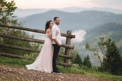 Abrazo encantador de la novia su novio hermoso en montañas Paseo hermoso de los pares de la boda Gackground verde fotografía de archivo