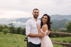 Abrazo encantador de la novia su novio hermoso en montañas Paseo hermoso de los pares de la boda Gackground verde imágenes de archivo libres de regalías