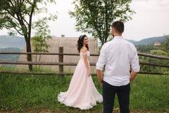 Abrazo encantador de la novia su novio hermoso en montañas Paseo hermoso de los pares de la boda Gackground verde foto de archivo libre de regalías