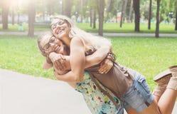 Abrazo feliz de dos chicas jóvenes en parque del verano fotografía de archivo