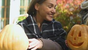 Abrazo feliz de la madre y de la hija, haciendo las calabazas talladas para el partido de Halloween almacen de video