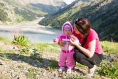 Abrazo feliz de la muchacha de la mamá y del niño. Madre hermosa y su bebé al aire libre Imagen de archivo libre de regalías