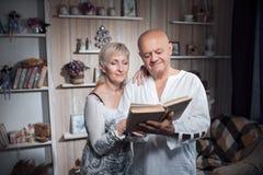 Abrazo feliz de los pares de los mayores y libro leído; Imagen de archivo libre de regalías