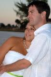 Abrazo feliz de los pares en la playa Imagen de archivo