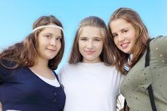 Abrazo feliz de tres muchachas en el fondo del cielo Imagenes de archivo