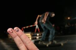 Abrazo feliz del dedo delante de un patinador urbano Fotografía de archivo