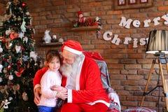 Abrazo fuerte entre el niño femenino feliz de la muchacha y Santa Cla Imagen de archivo