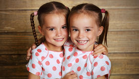Abrazo gemelo de las hermanas de los niños felices de la familia Fotografía de archivo libre de regalías