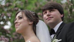 Abrazo hermoso del novio su novia hermosa Recienes casados que caminan en el parque Mujer del pelo de Brown en vestido que se cas almacen de metraje de vídeo