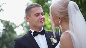 Abrazo hermoso del novio su novia hermosa Recienes casados que caminan en el parque Mujer del pelo rubio en vestido que se casa e almacen de video