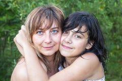Abrazo joven de la madre con su hija adolescente Fotografía de archivo libre de regalías