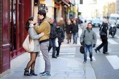 Abrazo joven de los pares de la datación en una calle de París, Francia Foto de archivo libre de regalías