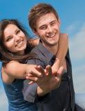 Abrazo joven feliz de los pares y cielo azul Imagen de archivo libre de regalías