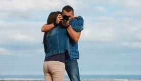 Abrazo joven hermoso de los pares, celebrando la cámara imagen de archivo libre de regalías