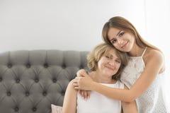 Abrazo maduro de la mujer con la muchacha adolescente joven Imagenes de archivo