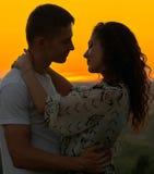 Abrazo romántico de los pares en la puesta del sol en el paisaje al aire libre, hermoso y el cielo amarillo brillante, concepto d foto de archivo libre de regalías