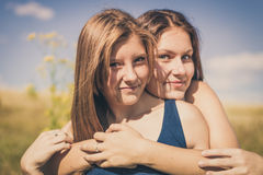 Abrazo sonriente feliz de dos muchachas sobre el cielo azul Imágenes de archivo libres de regalías