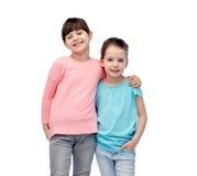 Abrazo sonriente feliz de las niñas imagenes de archivo