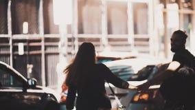 Abrazo y beso románticos jovenes de los pares en la calle Hombre caucásico con el paseo de la guitarra y de la mujer que lleva a  almacen de metraje de vídeo
