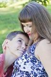 Abrazos cariñosos de la madre con el hijo del adolescente Fotos de archivo
