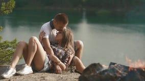Abrazos de los pares de Enloved mientras que se relaja en el sitio para acampar en rivershore del bosque metrajes