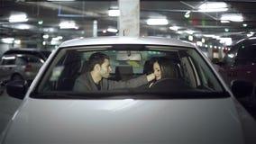 Abrazos de los pares en el coche en el estacionamiento subterráneo metrajes
