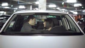 Abrazos de los pares en el coche en el estacionamiento subterráneo almacen de video