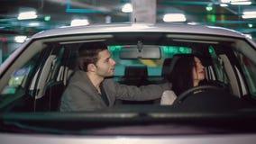 Abrazos de los pares en el coche en el estacionamiento subterráneo almacen de metraje de vídeo