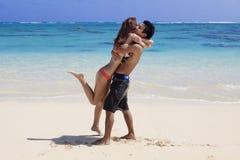 Abrazos de los pares en la playa en Hawaii Foto de archivo libre de regalías