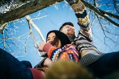 Abrazos de los pares de la felicidad El hombre joven abraza a la muchacha en rama de árbol imagen de archivo