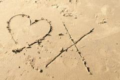 Abrazos del amor en la arena, el corazón y la marca de x imagen de archivo