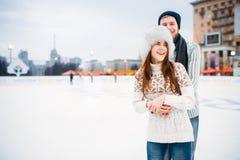 Abrazos felices de los pares del amor en pista de patinaje Imagen de archivo libre de regalías