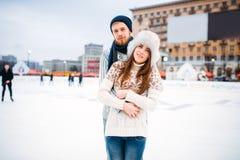 Abrazos felices de los pares del amor en pista de patinaje Fotos de archivo libres de regalías