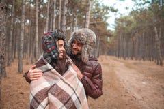 Abrazos felices y miradas de un par en uno a mientras que en el bosque al aire libre imagenes de archivo