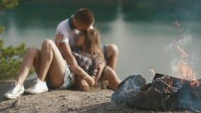 Abrazos jovenes cariñosos de los pares del adolescente mientras que se relaja en el sitio para acampar en rivershore del bosque metrajes