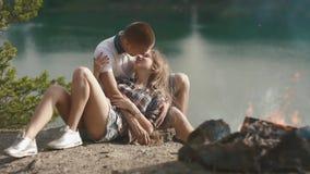 Abrazos jovenes cariñosos de los pares del adolescente mientras que se relaja en el sitio para acampar en rivershore del bosque almacen de metraje de vídeo