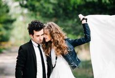 Abrazos lindos de los pares El retrato del hombre joven elegante en traje con el lazo abraza a la muchacha hermosa que sostiene e imagenes de archivo
