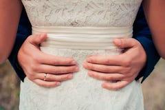 abrazos Men& x27; brazo de s alrededor del woman& x27; cintura de s Foto de archivo libre de regalías