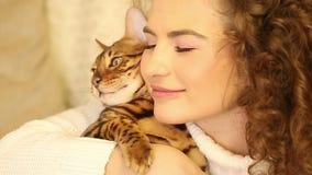 Abrazos y besos de la muchacha un gato de Bengala pet metrajes