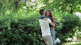 Abrazos y giros del individuo en su muchacha bonita de los brazos en el parque almacen de video