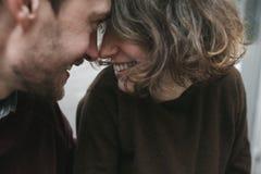 Abrazos y risa de los pares del vintage Tazas de café y granos de café frescos alrededor Fotografía de archivo