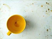 Abreibungsstillleben, leerer gelber keramischer Becher der Teeschale auf abgenutztem schmutzigem beflecktem weißem Brett, Draufsi stockfoto